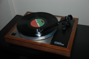 A record player with an album on it - notice the small spindle in the centre that you put the record on. (Photo; lockestreetaudio.com)
