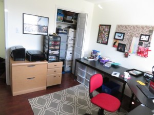 Home office with desk, chair, rug, filing cabinets and closet full of boxes