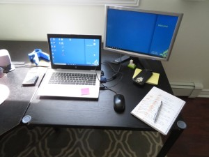 Small desk with laptop, external monitor, notebook and pen